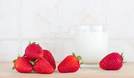 Some strawberries and a glass of milk. A composition with some strawberries and a glass of fresh milk on a wooden chopping board, inside a kitchen, landscape cut Royalty Free Stock Photo