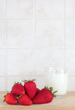 Some strawberries and a glass of milk. A composition with some strawberries and a glass of fresh milk on a wooden chopping board, inside a kitchen, space for royalty free stock photo