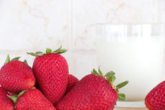 Some strawberries and a glass of milk. Detail of a composition with some strawberries and a glass of fresh milk on a wooden chopping board, inside a kitchen Stock Images