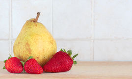 Some strawberries and a pear, space for text. A composition with some strawberries and a pear on a wooden chopping board, inside a kitchen, space for text on the Royalty Free Stock Photos