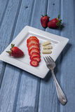 Some strawberries and pepperjack cheese. Strawberries, sliced and whole, are on a plate with some cheese Royalty Free Stock Images