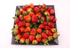 Some of strawberries top view. Fresh strawberries fruits on modern dish over white background royalty free stock photo
