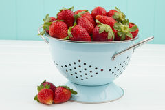 Some strawberries on a turquoise colander. A white wooden table with a turquoise background royalty free stock photography