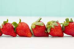 Some strawberries. On a white table with a turquoise background royalty free stock images