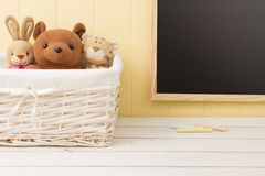 Some stuffed animal toys in the school. Some stuffed animal toys in a basket. A chalkboard in the background. Back to school Stock Images