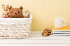 Some stuffed animal toys in the school. Breakfast. Some stuffed animal toys in a basket, chocolate chip cookies and a mug on a pile of notebooks. Back to school Royalty Free Stock Photo
