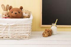 Some stuffed animal toys in tha school. Breakfast. Some stuffed animal toys in a basket, chocolate chip cookies and a school milk bottle with a straw. A Royalty Free Stock Photography