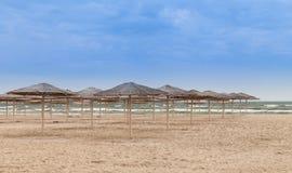 Some sun umbrellas on empty beach. Sun umbrellas on empty beach Royalty Free Stock Photo