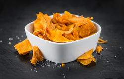 Some Sweet Potato Chips on a dark slate slab. Some fresh Sweet Potato Chips on a vintage slate slab, selective focus, close-up shot Stock Photos
