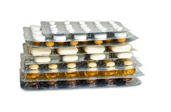 Some tablets blister packs stacked. Some tablets blister packs with various pills and capsules stacked and isolated on white background stock images