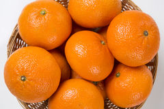 Some tangerines in a basket over a white background. Stock Photo