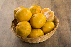Some tangerines in a basket over a wooden surface Royalty Free Stock Images