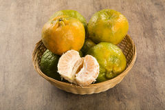 Some tangerines in a basket over a wooden surface. Fresh fruits Royalty Free Stock Image