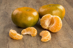 Some tangerines in a basket over a wooden surface. Fresh fruits Stock Photos