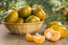 Some tangerines in a basket over a wooden surface. Fresh fruits Stock Photo
