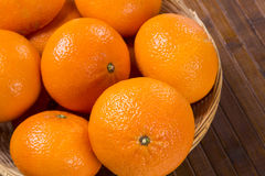 Some tangerines in a basket over a wooden surface. Fresh fruits Royalty Free Stock Images