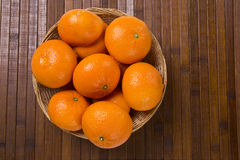 Some tangerines in a basket over a wooden surface Stock Photo