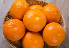 Some tangerines in a basket over a wooden surface. Fresh fruits Royalty Free Stock Photo