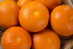 Some tangerines in a basket over a wooden surface. Fresh fruits Stock Image
