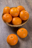 Some tangerines in a basket over a wooden surface Royalty Free Stock Photos