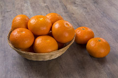 Some tangerines in a basket over a wooden surface Stock Photos