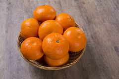 Some tangerines in a basket over a wooden surface Stock Image