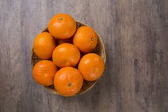 Some tangerines in a basket over a wooden surface Stock Images