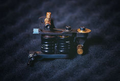 Some tattoo machine - frame with coils lying on a black, texture. D foam rubber Royalty Free Stock Image