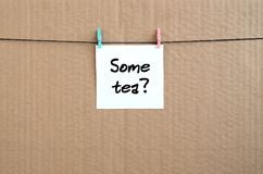 Some tea? Note is written on a white sticker that hangs with a c. Lothespin on a rope on a background of brown cardboard royalty free stock photos