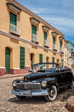 Some of them do sparkle -Vintage car in Trinidad. Trinidad, Cuba -March 8, 2016:  Beautiful vintage car used as taxi and at the back the side facade of Palacio Royalty Free Stock Photography