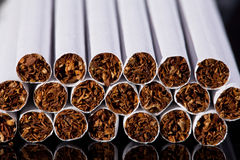 Some thin cigarettes on black background close up. Group of thin cigarettes on black background close up royalty free stock photo