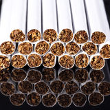 Some thin cigarettes on black background close up. Some thin cigarettes on black background with reflection close up royalty free stock image