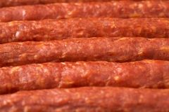 Some thin smoked sausages in a row close-up. A few thin smoked sausages in a row close up Royalty Free Stock Images