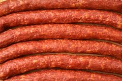 Some thin smoked sausages in a row close-up. A few thin smoked sausages in a row close up royalty free stock photos