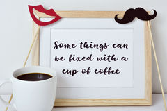 Some things can be fixed with a cup of coffee. A wooden-framed picture with the text some things can be fixed with a cup of coffee written in it, a red mouth and royalty free stock photo
