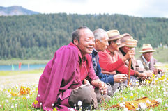 Some Tibetans chatting, sitting on the prairie. Prairie full of flowers ,High Mountain and Lake Cuopu ,Batang country Tibet Stock Image
