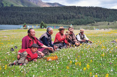 Some Tibetans chatting, sitting on the prairie. Prairie full of flowers ,High Mountain and Lake Cuopu ,Batang country Tibet Royalty Free Stock Images