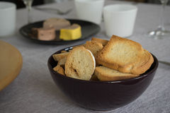 Some toast and pates. Bowl with toast and a cheese plate at the bottom Royalty Free Stock Images