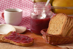 Some toasted bread slices with some marmalade spread. Wooden table in a rustic kitchen stock images