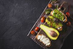 Some toasted with green avocado on black texture. Copy space royalty free stock photography