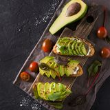 Some toasted with green avocado on black texture. Copy space, square royalty free stock photos