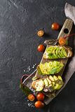 Some toasted with green avocado on black texture. Copy space, vertical royalty free stock photos