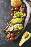 Some toasted with green avocado on black texture. Copy space, vertical stock image