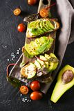 Some toasted with green avocado on black texture. Copy space, vertical royalty free stock photography