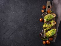Some toasted with green avocado on black texture. Copy space stock images
