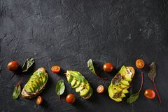 Some toasted with green avocado on black texture. Copy space stock photos