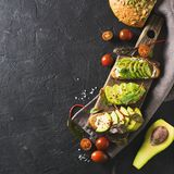 Some toasted with green avocado on black texture. Copy space, square royalty free stock images