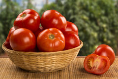 Some tomatoes over a wooden background. Fresh vegetable royalty free stock image