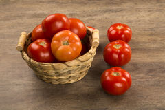 Some tomatoes over a wooden background. Fresh vegetable royalty free stock photos