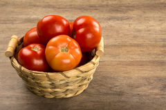 Some tomatoes over a wooden background. Fresh vegetable royalty free stock photography